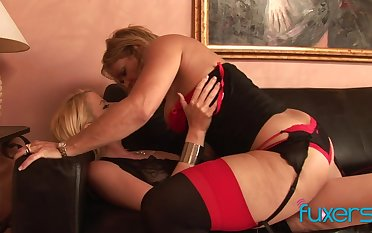 Curvaceous temptress of a MILF fucks a pretty young woman beside a strap-on